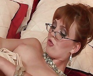 Redhead mature in glasses drills her trimmed pussy with a toy